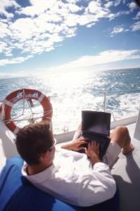 Man sitting on deck of sailboat using laptop